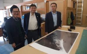 "Panasonic Lumix executives Shinji Watanabe, Henri Nishikawa and Yasuhide Yamada take time out to review one of Daniel's newest print newest print releases ""Raven Spirit"" at the Natural Exposures office in Bozeman, Montana"